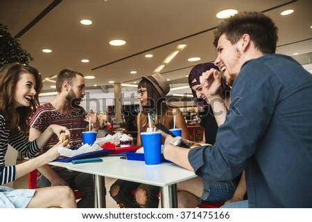 Hipster Friends In Fast Food Restaurant Having Lunch - stock photo