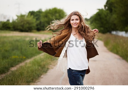 Hipster girl dancing and laughing on the road
