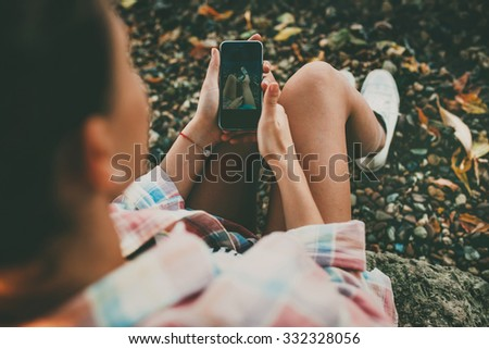 Hipster girl holding a smartphone outdoors. Young woman taking a feet selfie on rocky background on autumn day. - stock photo