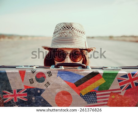 Hipster girl in a hat and sunglasses looks out from vintage suitcase. Suitcase with stamps flags of different country - stock photo