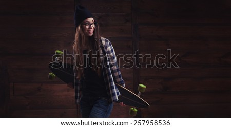 Hipster girl in glasses and black beanie with longboard on the wooden background