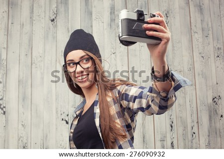 Hipster girl in glasses and black beanie with vintage camera on the wooden background - stock photo