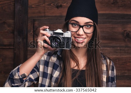 Hipster girl in glasses and braces with vintage camera on the wooden background - stock photo
