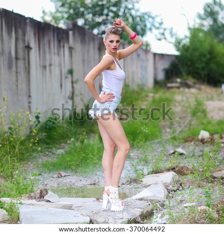 hipster girl in shorts and a t-shirt posing on the background of slums. Outdoors lifestyle