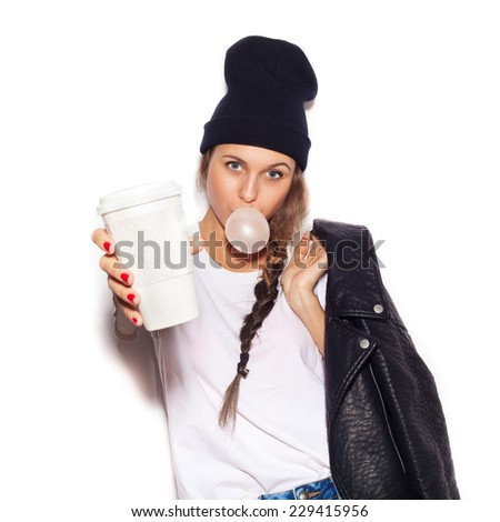Hipster girl inflating chewing gum and holding cup of coffee. Close-up lifestyle indoor portrait, not isolated - stock photo