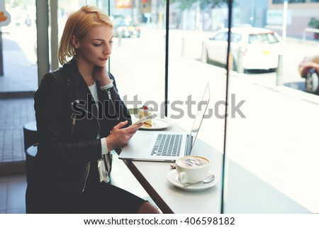 Hipster girl is reading text message on cell phone, while is watching on-line training in network via laptop computer. Business woman is sitting in coffee shop with cup of cappuccino during work break