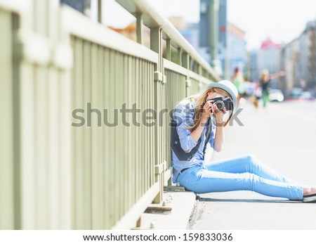 Hipster girl making photo with retro camera while sitting on city street - stock photo