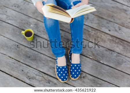 hipster girl reading open book on a wooden floor - stock photo