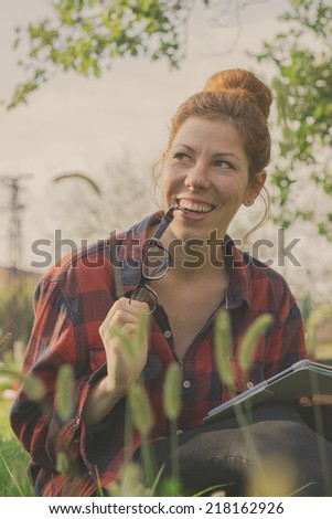 Hipster girl using tablet computer, sitting in the grass on a beautiful sunny day. Retro colors - stock photo