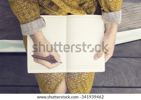 Hipster girl with blank diary and pen sitting on wooden bench - stock photo