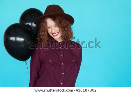 Hipster girl with curly hairstyle and stylish hat holding hot air balloons. Beautiful young woman with black balloons isolated on blue background with copy space. - stock photo
