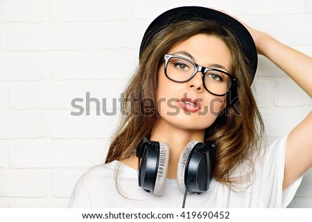 Hipster girl with headphones stands by a white brick wall. - stock photo