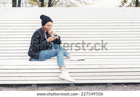 Hipster girl with phone reading text on a white bench in the park.  Outdoors lifestyle portrait of young woman - stock photo