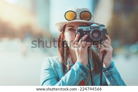 Hipster girl with retro camera. Focus on camera - stock photo