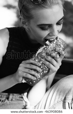 Hipster girt posing eating big sandwich. Outdoors lifestyle portrait. Black and white photography