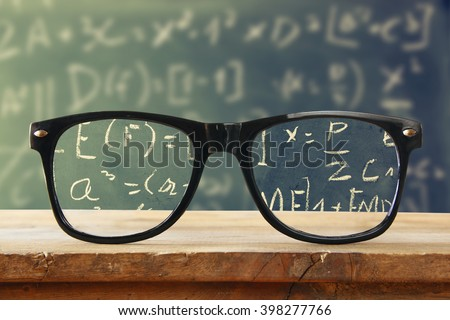 hipster glasses on a wooden rustic table in front blackboard with math formulas and calculation. vintage filtered  - stock photo