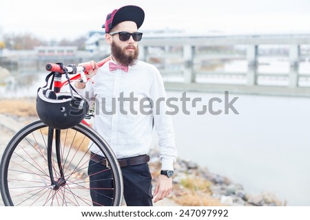 Hipster guy in glasses holding a bike. - stock photo