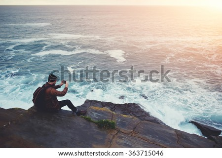 Hipster guy taking pictures of amazing landscape on mobile smart phone digital camera while sitting on a rock near the sea, beautiful sunset light create background with copy space for text message  - stock photo