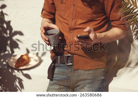 hipster guy using his smart phone outdoors and relaxing - stock photo
