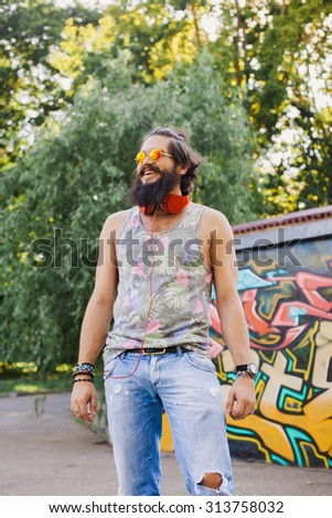 Hipster hair and beards,Happy young man.Portrait of handsome young man in casual shirt keeping arms crossed and smiling while standing against grey background.Big earphones,favorite music,mans   - stock photo