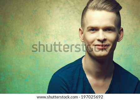 Hipster haircut concept. Portrait of young man in blue t-shirt with stylish haircut posing over golden-turquoise  background and smiling. Perfect skin & hair. Close up. Copy-space. Studio shot - stock photo