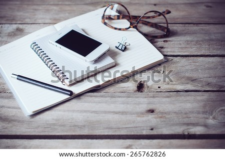 Hipster home office tabletop: papers and notebooks, reading glasses, smart phone, pen on an old wooden board background. Vintage lifestyle. - stock photo