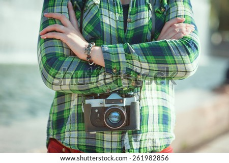 Hipster in green checkered shirt with retro camera outdoor - stock photo