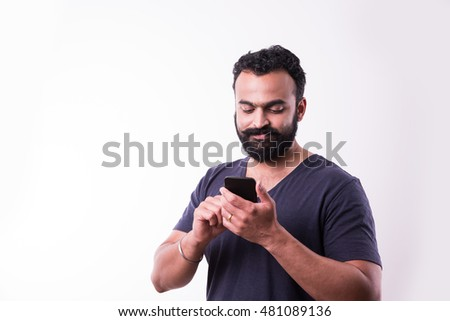 hipster indian young man with beard and mustache busy using smartphone, isolated over white background