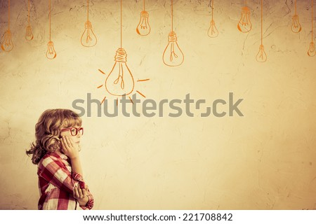 Hipster kid thinking. Idea concept. Drawing bulb lump. Retro toned - stock photo