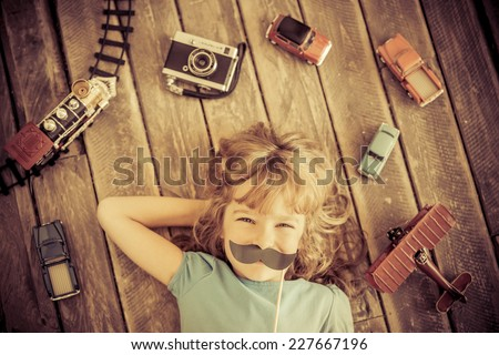 Hipster kid with vintage wooden toys at home. Girl power and feminism concept - stock photo