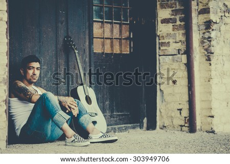 Hipster male with tattoos with guitar
