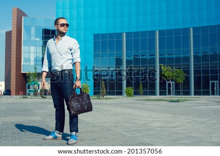 Hipster Man Concept. Portrait of attractive guy in trendy casual clothing with leather bag and sunglasses posing over shopping mall. Sunny summer weather with blue sky. Outdoor shot - stock photo