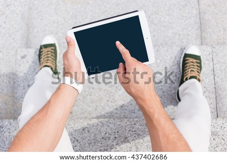 Hipster man hands holding digital tablet with empty blank screen for your text message, business person browsing internet or connecting to wireless via touchscreen pad   sitting outdoors - stock photo