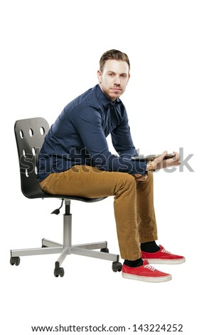 Hipster man in bow tie looking stylish using tablet white sitting on chair - stock photo