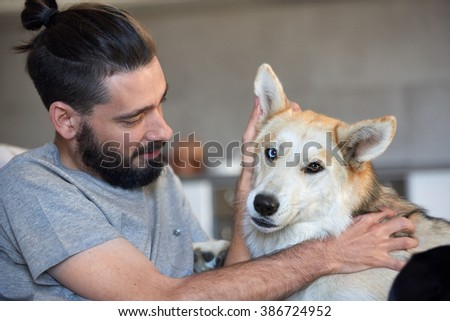 hipster man petting and rubbing his dog, loving affection best friend bond between owner and pet