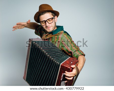 hipster man plays on the bayan, wearing a hat and glasses, isolated on a gray background - stock photo