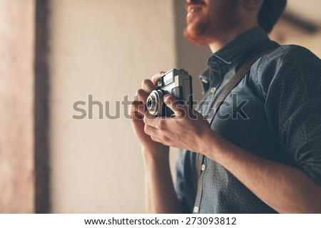 Hipster man searching for an interesting subject for his photo shooting and holding a vintage camera - stock photo