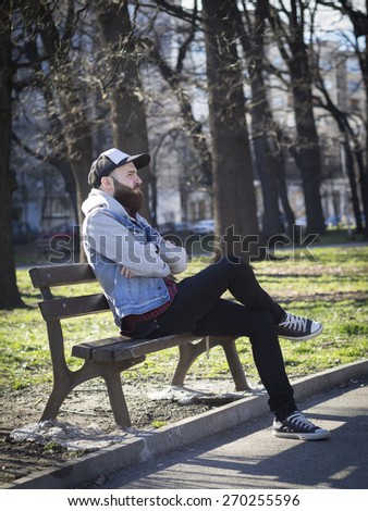 Hipster man sitting on a wooden bench in the park, vertical. - stock photo
