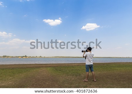 Hipster man taking photos with camera at the beach in asia