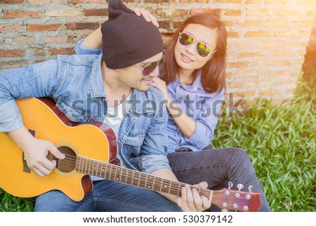 Hipster man teach playing the guitar to his girlfriend while sitting in the grass look so happy. Couple in love concept.