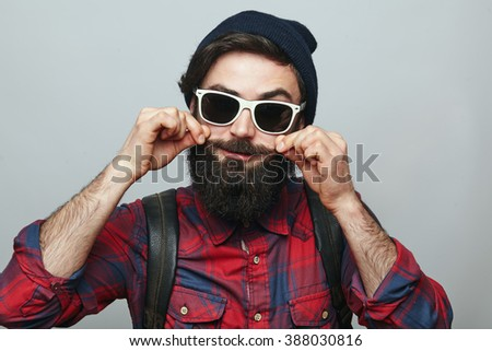 Hipster man with beard wearing sunglasses adjusting his mustaches while standing against grey background - stock photo