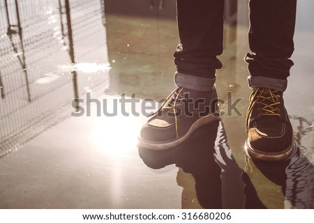 Hipster man with fashion brown leather boots on wet floor - stock photo