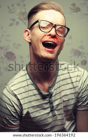 Hipster Maniac Concept. Portrait of smiling young crazy man in trendy glasses with fake blood on his face. Halloween costume and make-up. Vintage (old slasher movie) style. Close up. Studio shot - stock photo