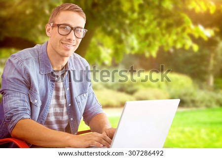 Hipster on laptop against trees and meadow in the park
