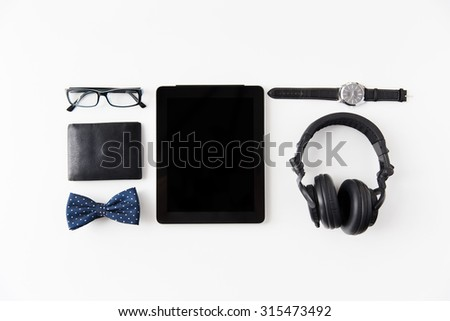 hipster personal stuff and objects concept - tablet pc computer, earphones, wallet, eyeglasses and wristwatch on table - stock photo