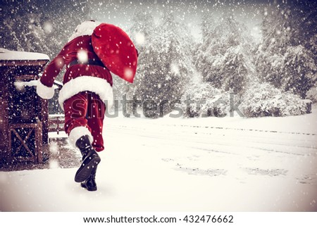hipster photo of landscape of snow and brown old home and santa claus and sack  - stock photo