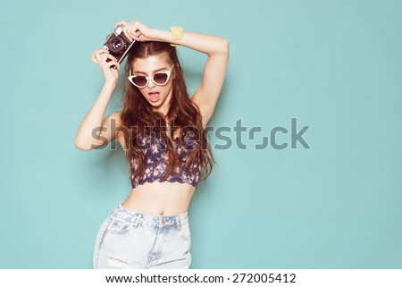 hipster photographer fashion stylish woman dancing and making photo using retro camera. Portrait on blue background  - stock photo