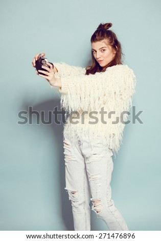 hipster photographer fashion stylish woman dancing and making self photo using retro camera. Portrait on blue background in white sweater - stock photo