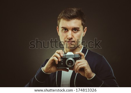 hipster photographer in studio with retro camera in hand