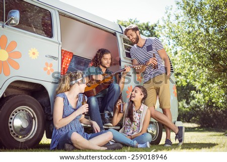 Hipster playing guitar for his friends on a summers day - stock photo